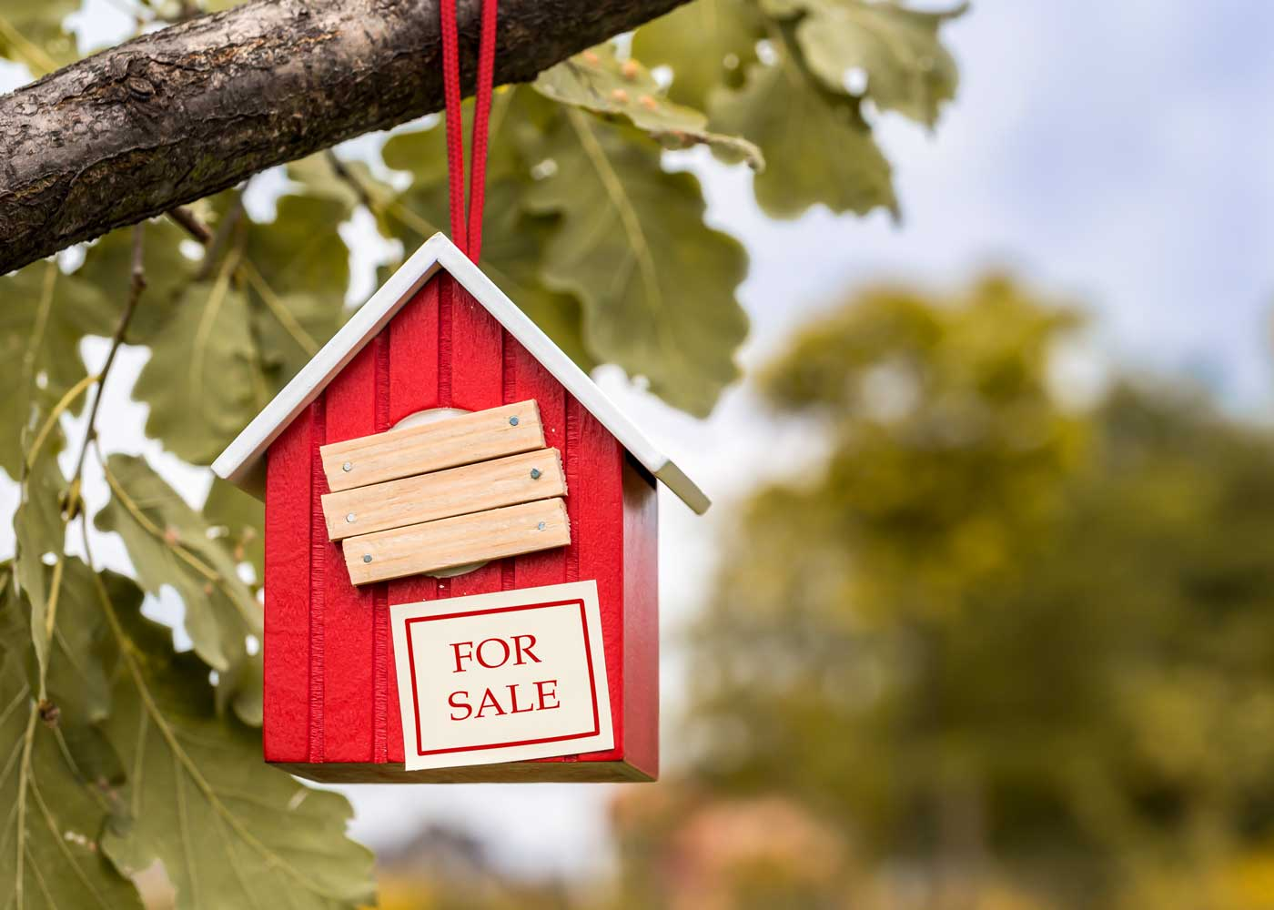 "A red birdhouse with a ""for sale"" sign."