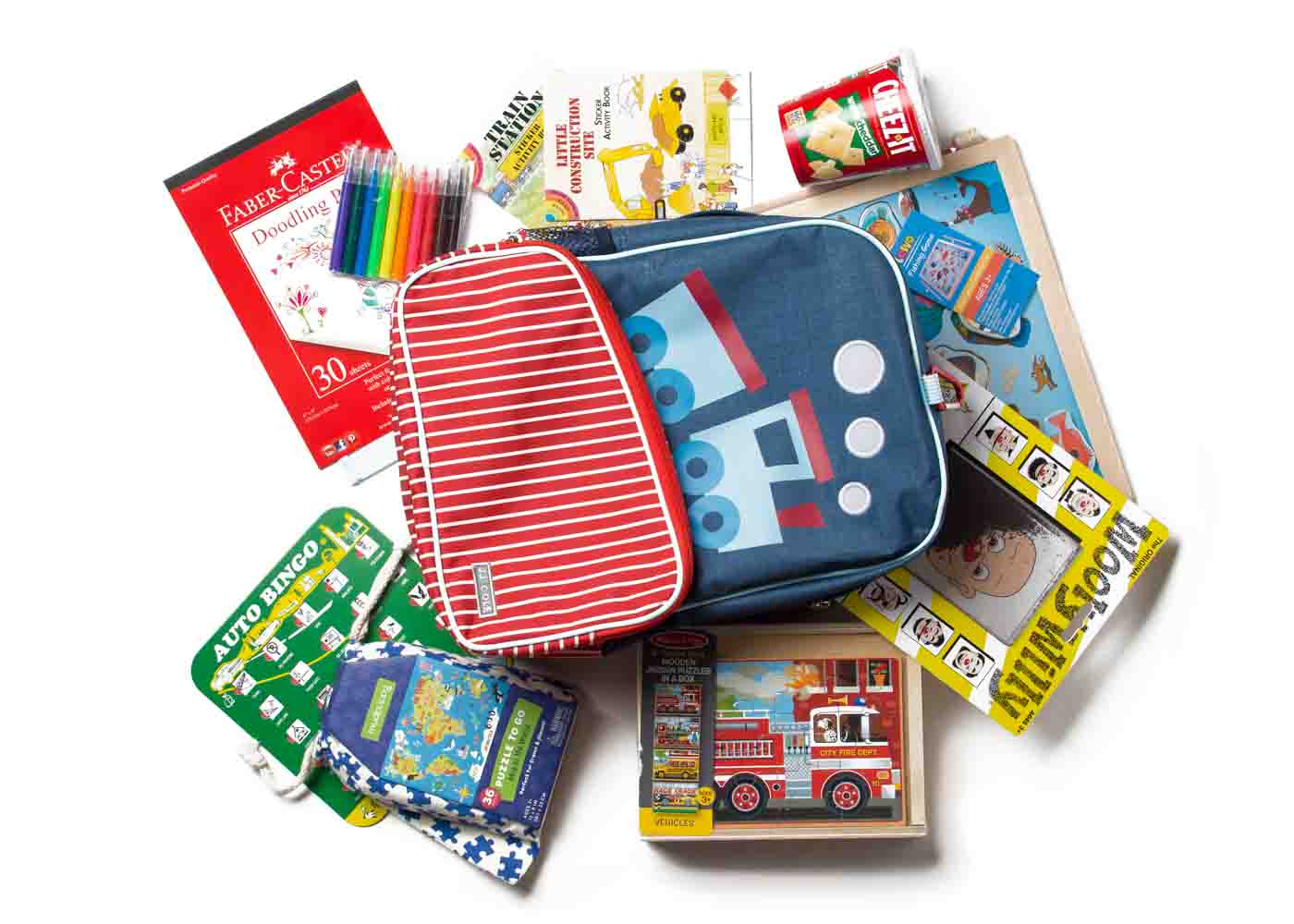 Filling a JJ Cole's train knapsack with travel-friendly games and toys for children.