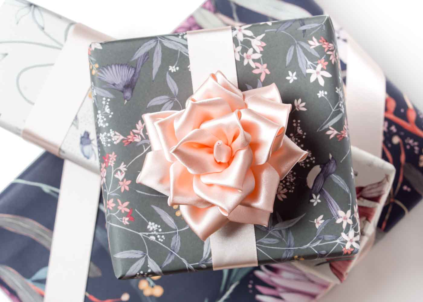 A rose of pink satin ribbon that we made following a DIY YouTube tutorial by The Flower Art.