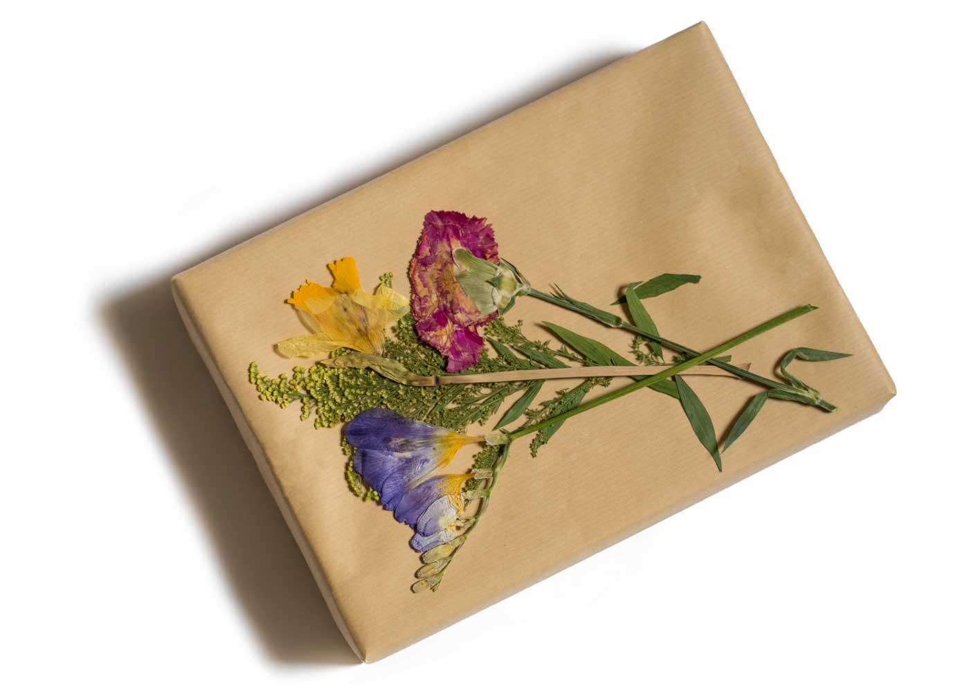 Garnishing a gift with a selection of dried flowers.