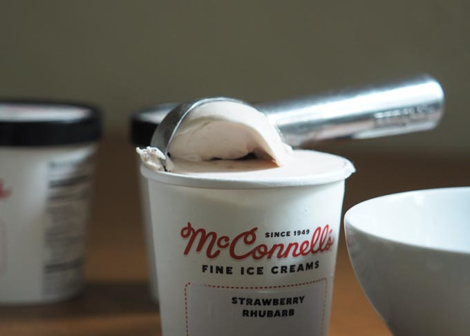 Scooping a pint of McConnell's Strawberry Rhubarb ice cream.