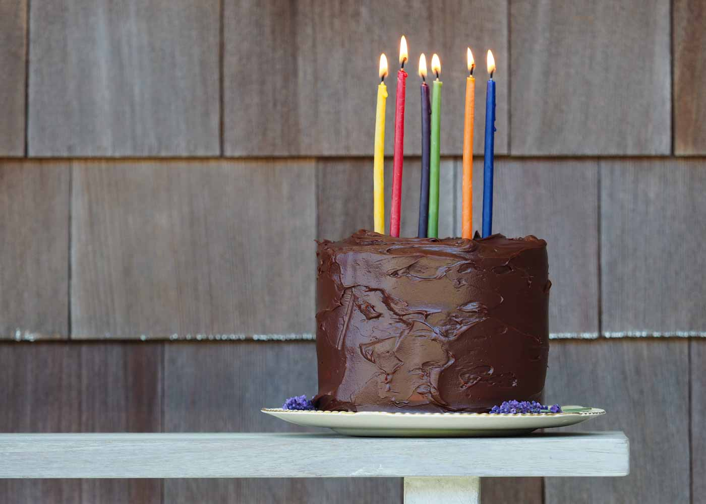Pioneer Candle's beeswax birthday candles atop a white cake with chocolate ganache frosting.